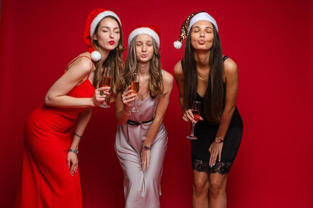 Drie vrolijke vriendinnen in prachtige jurken vieren nieuwjaar en verheugt zich samen