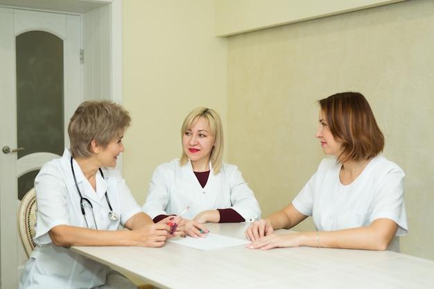 Drie vrouwelijke arts in witte jassen zitten aan de tafel in de kliniek op kantoor