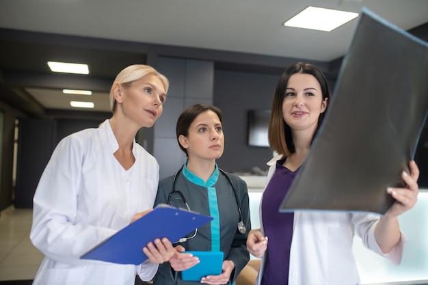 Drie vrouwelijke artsen die betrokken kijken tijdens het bespreken van xray-resultaten