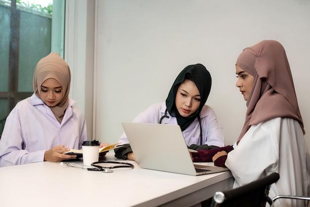 Drie vrouwelijke artsen die samenwerken, raadplegen over patiëntengeval, in het ziekenhuis