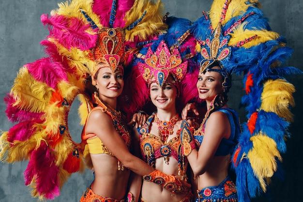 Drie vrouwelijke dansers in braziliaans samba-carnavalkostuum met kleurrijk verenkleed