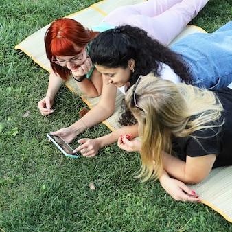 Drie vrouwelijke vrienden liggen op gras en kijken naar het smartphonescherm