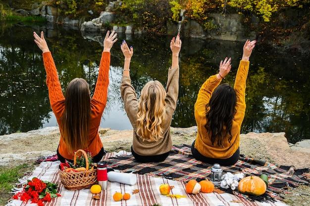 Drie vrouwen beste vrienden bij herfstpicknick in het park. kleurrijke plaid, thermoskan en pumpins. vrienden plezier buitenshuis. warme herfst oktober dag