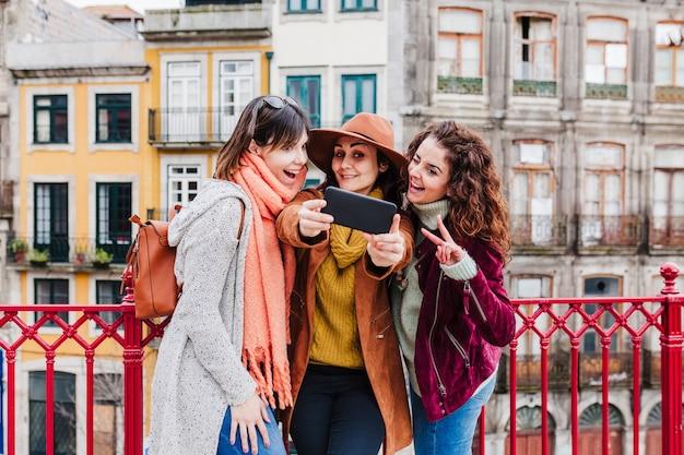 Drie vrouwen die het uitzicht op porto bekijken en een foto maken met een mobiele telefoon. reis- en vriendschapsconcept