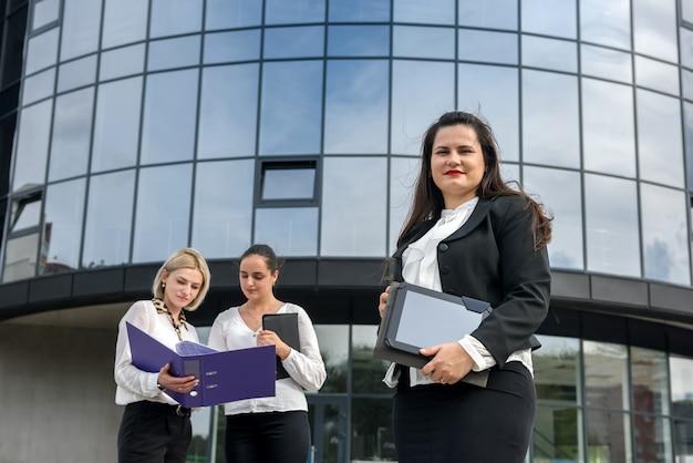 Drie vrouwen die informatie in omslag lezen. ze staan buiten het kantoorgebouw en zijn gekleed in pakken