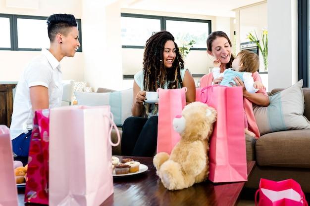 Drie vrouwen die op een laag zitten die bij een baby glimlachen die door giften wordt omringd