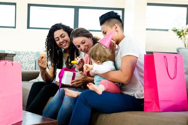 Drie vrouwen die op een laag zitten die de eerste verjaardag van een baby viert
