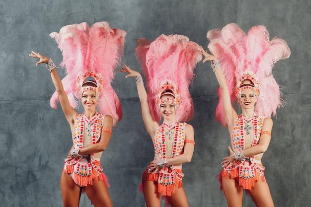 Drie vrouwen in braziliaans samba of lambada carnavalskostuum met roze veren verenkleed
