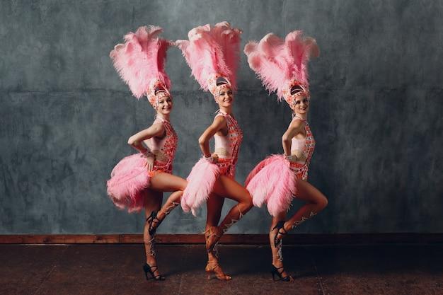 Drie vrouwen in cabaretkostuum met roze verenkleed.