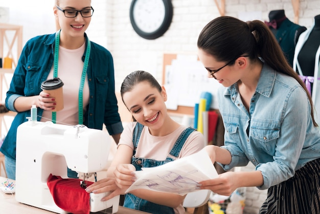 Drie vrouwen in de fabriek naaien nieuwe kleren.