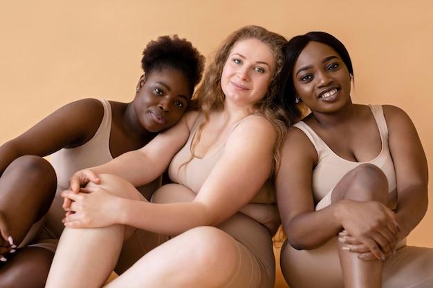 Drie vrouwen in naakte illusie body shapers die samen poseren