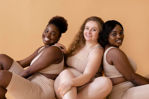 Drie vrouwen in naakte lichaamsvormers die samen poseren