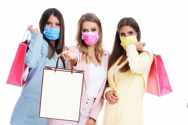 Drie vrouwen in pastel pakken met boodschappentassen op witte achtergrond