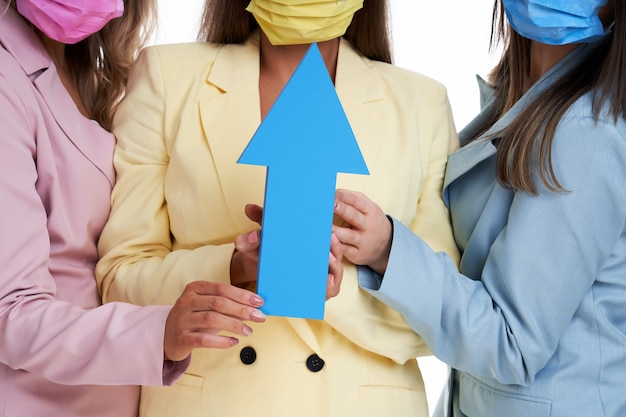 Drie vrouwen in pastel pakken poseren met pijlen op witte achtergrond