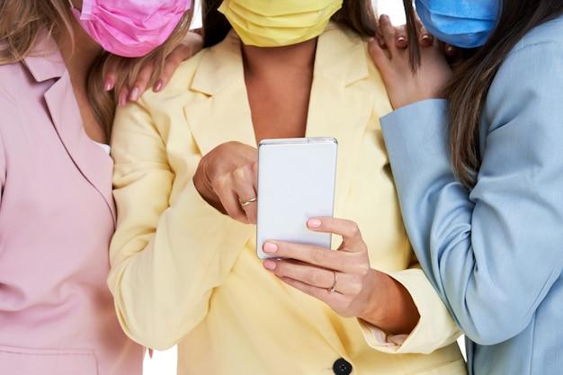 Drie vrouwen in pastel pakken poseren met smartphones op witte achtergrond