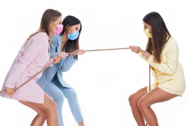 Drie vrouwen in pastelkleurige pakken die aan touw trekken en maskers dragen op een witte achtergrond