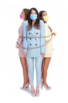 Drie vrouwen in pastelkleurige pakken die maskers dragen en gehinderd worden met touw poseren op een witte achtergrond