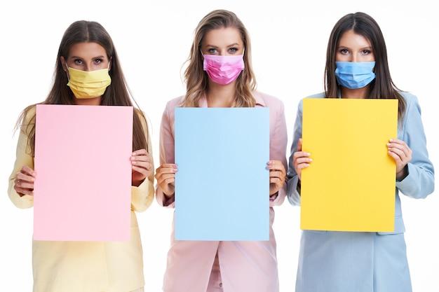 Drie vrouwen in pastelkleurige pakken met billboard poseren op een witte achtergrond