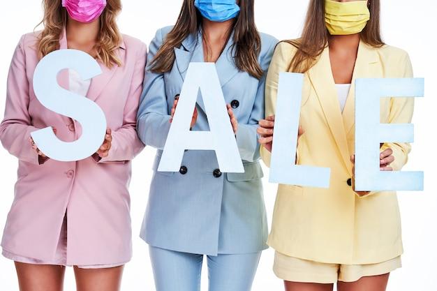 Drie vrouwen in pastelkleurige pakken met verkoopbrieven op een witte achtergrond