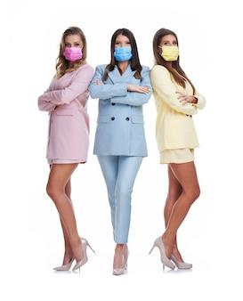 Drie vrouwen in pastelkleurige pakken poseren op een witte achtergrond