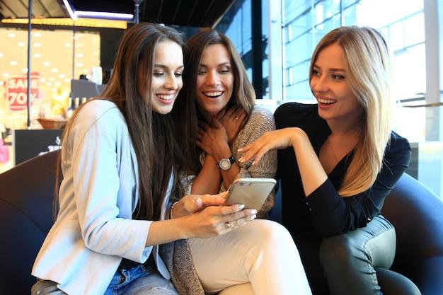 Drie vrouwen nemen een selfie tijdens het winkelen in een kledingwinkel. ze zijn blij en glimlachen naar de camera. winkelconcept, ook gerelateerd aan verslaving aan sociale media