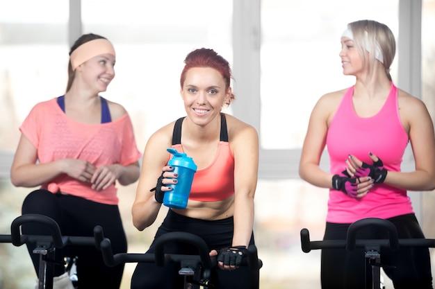Drie vrouwen ontspannen na cardio oefeningen op cycli