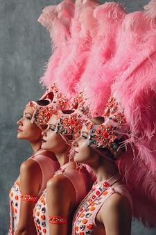 Drie vrouwen profiel portret in samba of lambada kostuum met roze veren verenkleed