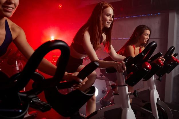 Drie vrouwen trainen graag op de hometrainer in de sportschool, intensieve cardiotraining in de sportschool. sport en een gezonde levensstijl concept