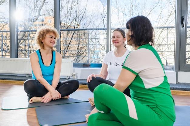 Drie vrouwen van middelbare leeftijd zitten op matten in lotus houding en bespreken yoga fitness oefeningen, groepstraining