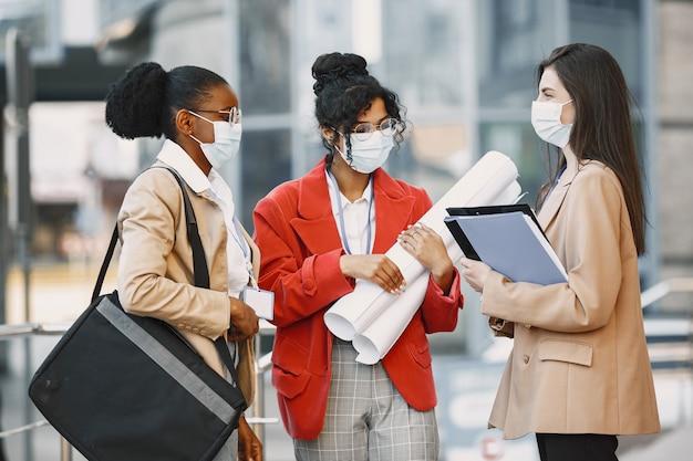 Drie vrouwen werken als architecten aan een vernauwing. mensen die een beslissing nemen over het plan van een gebouw. quarantaine concept