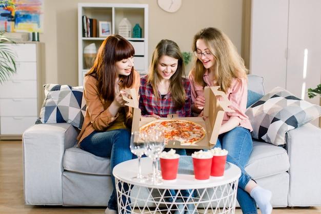 Drie vrouwenvrienden die diner hebben thuis. foto van vrolijk verrast meisjes vieren een feestje thuis, kartonnen doos openen met met pizza.