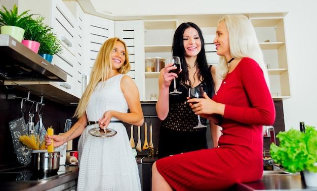 Drie vrouwenvrienden die pret in de keuken hebben en voedsel voorbereiden