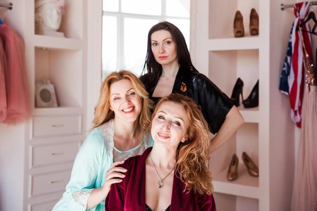 Drie vrouwenvrienden in kamerjassen die voor de camera stellen.