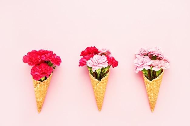 Drie wafel-ijshoorntjes met roze anjerbloemen op roze achtergrond bovenaanzicht kopie ruimte