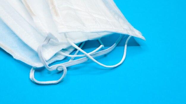 Drie wegwerp chirurgische gezichtsmaskers met rubberen pads om de mond en neus te bedekken op een blauwe achtergrond. het concept van bescherming tegen bacteriën, gezondheidszorg en medicijnen. covid-19. ruimte kopiëren.