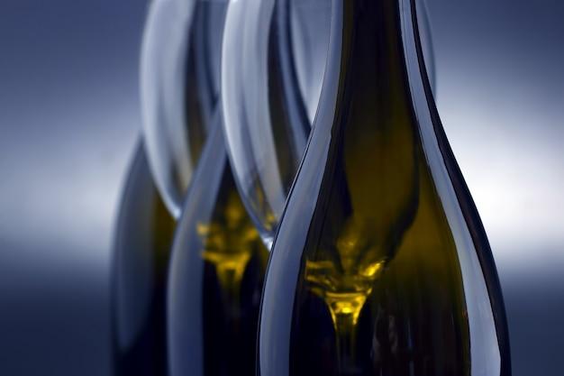Drie wijnflessen en twee lege wijnglazen sluiten omhoog