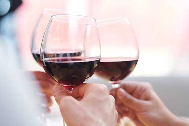 Drie wijnglazen met rode cabernet gehouden door roosterende vrienden die van feest genieten en vakantie vieren