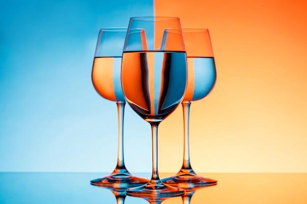 Drie wijnglazen met water over blauwe en oranje achtergrond.