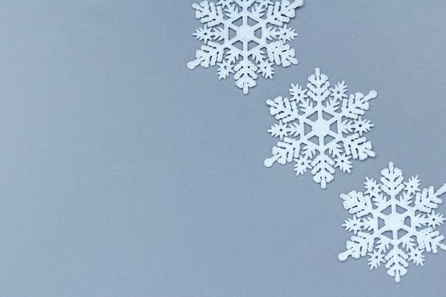 Drie witte decoratieve sneeuwvlokken op een grijze achtergrond. kerstmis en nieuwjaar, een plek voor tekst, minimalisme, winterachtergrond