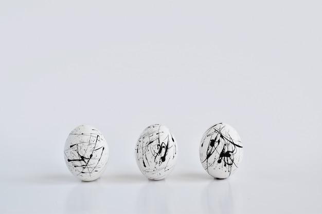 Drie witte eieren gespikkeld op wit. het minimale concept van pasen. pasen-wenskaart met een ruimte voor tekst. geometrie.
