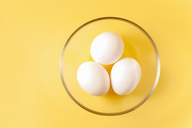 Drie witte eieren liggen in een ronde transparante glazen beker in het midden van een gele achtergrond.