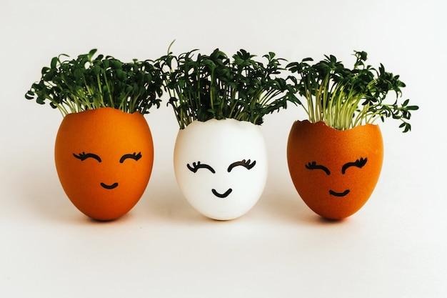 Drie witte eieren met zaailingen binnen met gezichten op de schaal geschilderd.