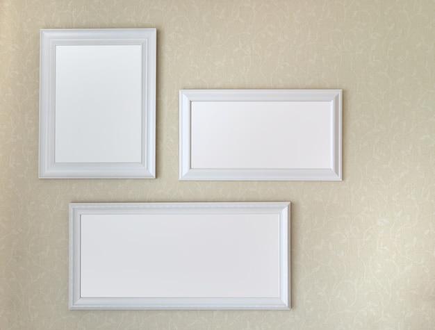 Drie witte houten kaders die op zachte gele muurspot op malplaatje hangen