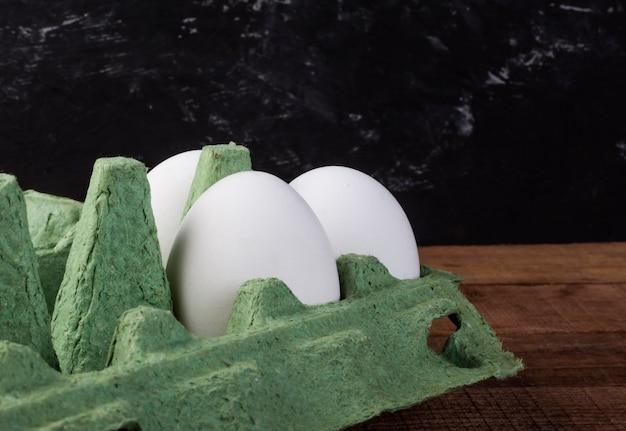 Drie witte kippeneieren in een groene container op een bruine houten tafel.