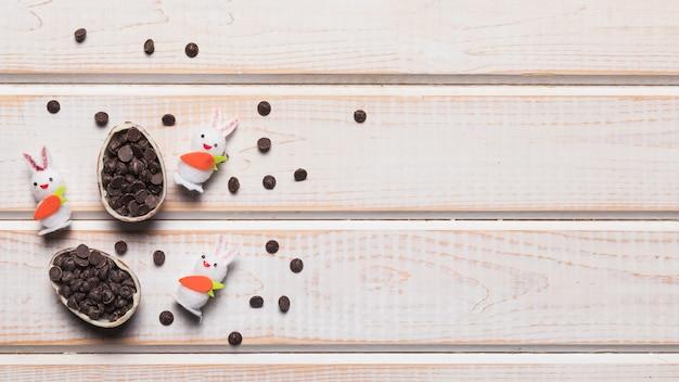 Drie witte konijntjes met gebroken die paasei met choco chips op houten bureau wordt gevuld