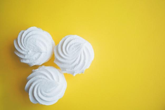 Drie witte weelderige verse marshmallows op een helder gele monochromatische achtergrond close-up met vrije ruimte aan de rechterkant