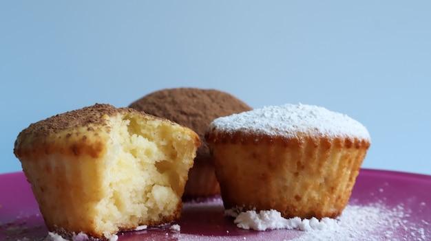 Drie wrongelcakes bestrooid met chocolade en poedersuiker, een van hen gebeten, op een roze bord, op een blauwe achtergrond close-up. dessert, een kleine cupcake. witgebakken koekjes met een luchtige structuur.