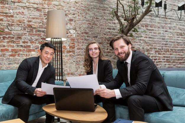 Drie zakenlieden, mannen en vrouwen kijken blij naar de camera Premium Foto