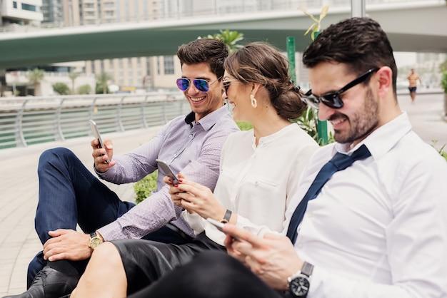 Drie zakenmensen in pak die een pauze nemen van hard werken. buiten zitten in dubai marina en lekker surfen op internet.