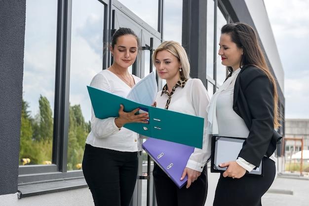 Drie zakenpartners met mappen poseren buiten kantoorgebouw